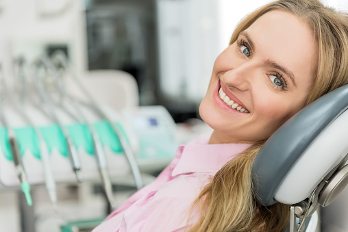 A woman sitting in a dental chair smiling during her consultation at Oral and Facial Surgery Center