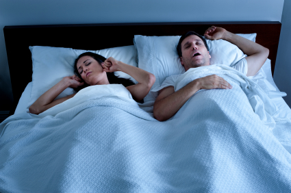 woman having trouble sleeping next to a snoring man with sleep apnea in Tallahassee, FL