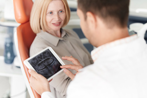 woman in dental chair with doctor reading xray on ipad in Tallahassee, FL